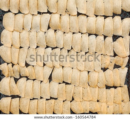 Closeup of raw prawn cracker slices arranged for sun drying on a tray.  - stock photo