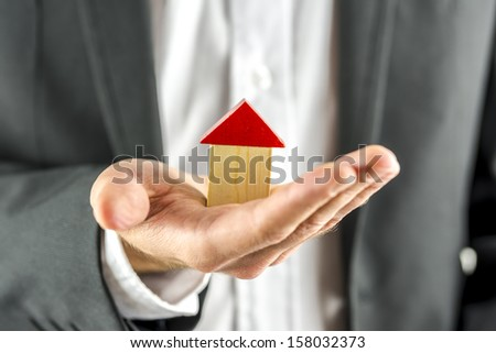 Closeup of real estate agent holding a wooden  house in his hand. Real estate business.