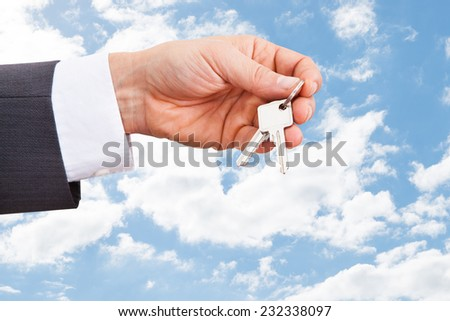 Closeup of real estate agent's hand holding keys against cloudy sky