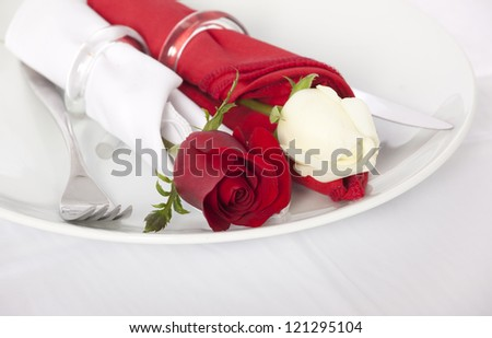 Closeup of red and white rose and cutlery on white plate