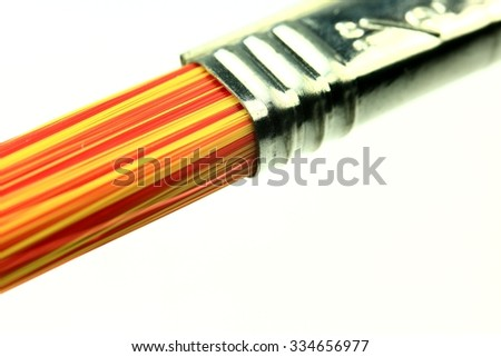 Closeup of red and yellow paintbrush with metal.