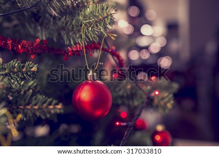 Closeup of red bauble hanging from a decorated Christmas tree. Retro filter effect. - stock photo