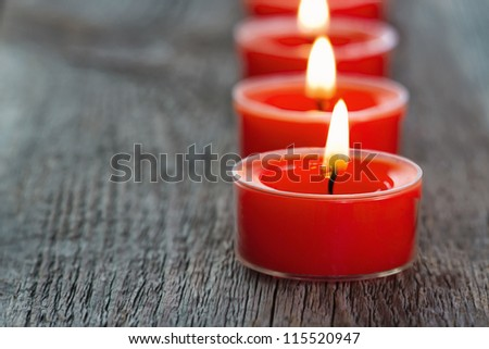 Closeup of red burning candles on a wooden rustic background