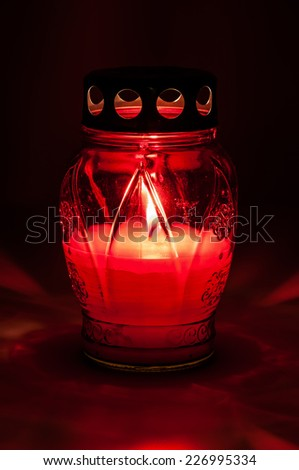 Closeup of red burning votive candle in the dark - stock photo