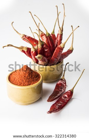 closeup of red chilly powder and stacked red chillies in brown ceramic bowl with 2 chillies kept near bowl on white background, isolated and vertical view, front view - stock photo