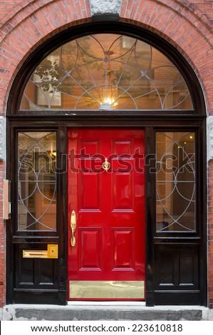 Closeup of Red Door In Black Archway Door Frame with Windows on Brick Building - stock photo