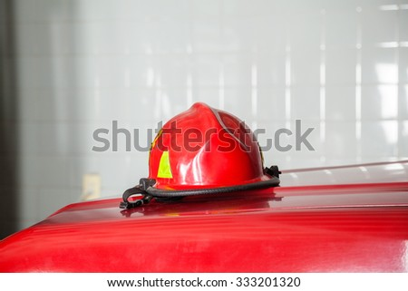 Closeup of red helmet on truck at fire station - stock photo