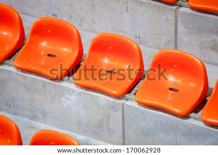 Closeup of red sport stadium seats. Empty stand. Team sport and football supporters fans.