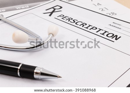 Closeup of red stethoscope and pen on a rx prescription. - stock photo