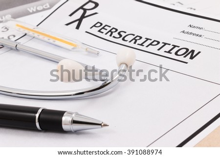 Closeup of red stethoscope, thermometer and pen on a rx prescription. - stock photo