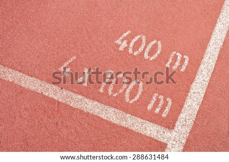 Closeup of red track lane, with 4x400m mark on the tarmac - stock photo