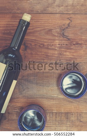 Closeup of red wine in blue glasses on a wooden table. Concept: dating, love, romance