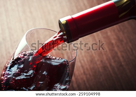 Closeup of red wine pouring in glass - stock photo
