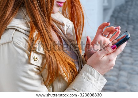 Closeup of redhair girl texting on mobile phone,closeup of the hands holding mobile device. red haired woman holding smart phone, phablet of small digital tablet in hands and using mobile internet app - stock photo