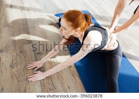 Closeup of redhead young woman training and stretching with trainer - stock photo