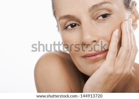 Closeup of relaxed middle aged woman with hand on chin over white background - stock photo