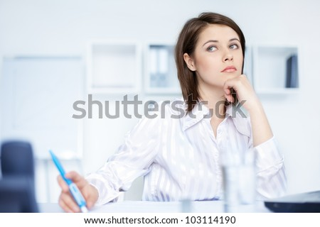 Closeup of relaxed young beautiful young business woman at office - stock photo