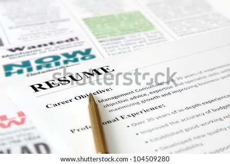 Closeup of resume with pen on the newspaper - stock photo