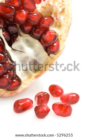 Closeup of ripe pomegranate seeds on white background.