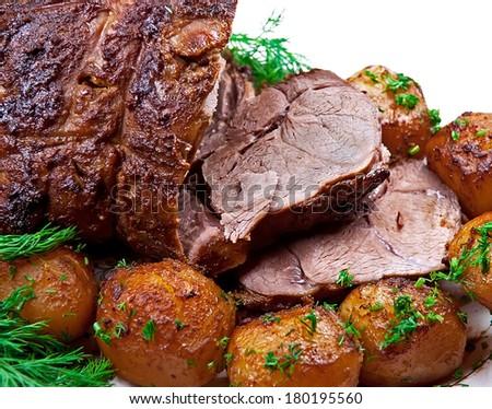 Closeup of roast  lamb with potatoes on white background. - stock photo