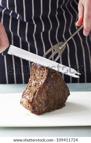 Closeup of roast meat ready to be carved by a chef - stock photo