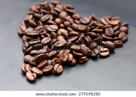 Closeup of roasted coffee beans on black background, selective focus - stock photo