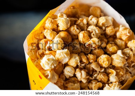 Closeup of roasted popcorns filled in paperbag at cinema theater - stock photo