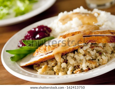 Closeup of roasted turkey with mashed potatoes, vegetables, stuffing and gravy. - stock photo