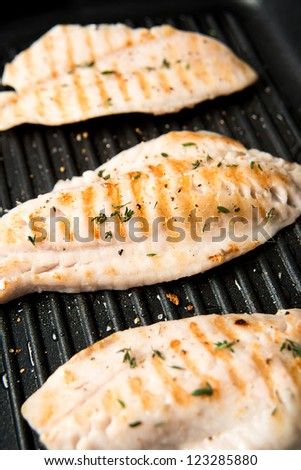 Closeup of Rock Fish Grilled on Griddle with Some Herbs and Spices - stock photo