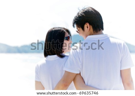 closeup of romantic couples, each other seeing eyes on the beach - stock photo