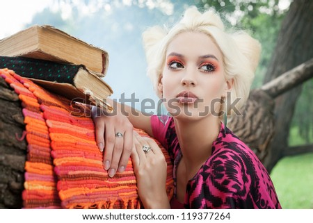 Closeup of romantic woman with books on a tree in a fairy foggy forest. Outdoors. - stock photo