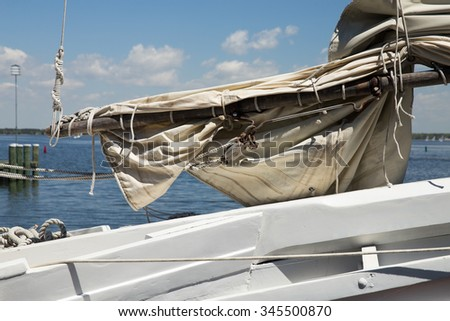 Closeup of sail tied to the mast of a wooden sailboat at the Chesapeake Bay Maritime Museum in St. Michael's, Maryland. - stock photo