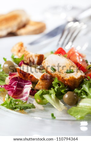 closeup of salad with grilled chicken breasts