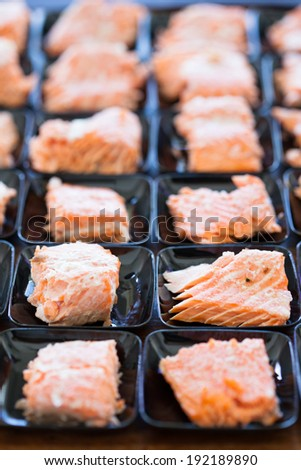 Closeup of salmon appetizers on small serving trays in rows - stock photo