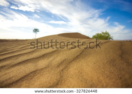 Closeup of sand dune in the Sahara desert close to Merzouga in Morocco with blue sky and clouds. Selective focus. - stock photo