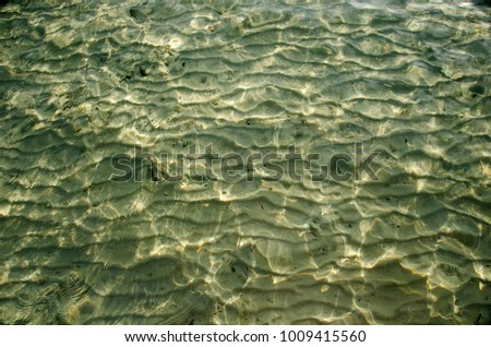 Closeup of sand pattern under sea with direct sun rise