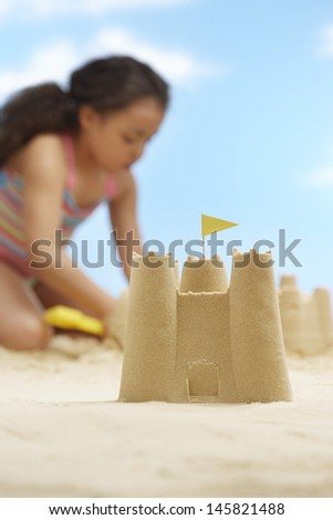 Closeup of sandcastle with girl playing in background on beach - stock photo