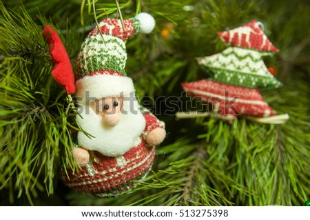 Closeup of Santa Claus Christmas-tree decoration hanging from a decorated Christmas tree.