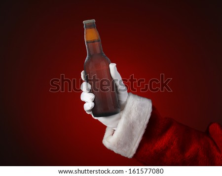 Closeup of Santa Claus holding a bottle of beer. Only hand and arm are visible. Horizontal format on a light to dark red spot background. - stock photo