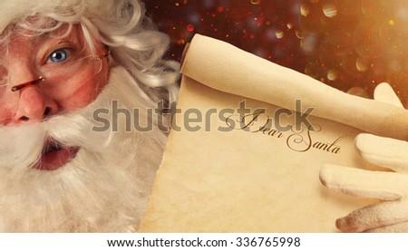 Closeup of Santa Claus holding a Dear Santa scroll  - stock photo
