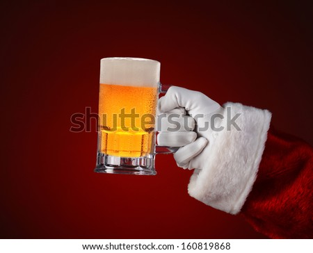 Closeup of Santa Claus holding a mug of beer. Horizontal format on a light to dark red spot background. - stock photo