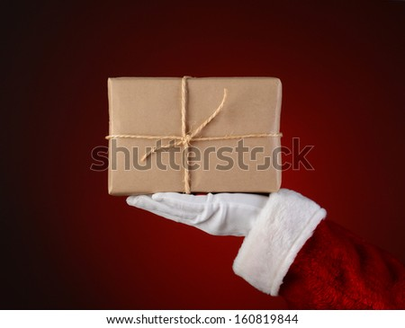 Closeup of Santa Claus holding a parcel in the palm of his outstretched hand. Hand and arm only over a light to dark red spot background. - stock photo