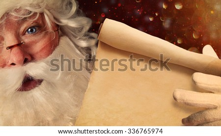 Closeup of Santa Claus holding a Santa List scroll  - stock photo
