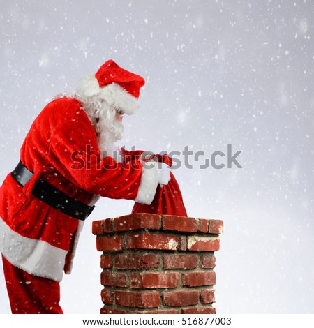 Closeup of Santa Claus placing his bag of toys into a chimney while it snows on Christmas Eve.