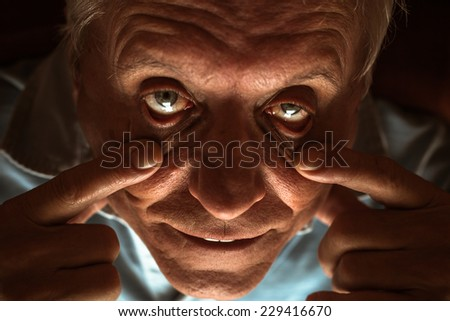Closeup of scary senior man showing his eyes - stock photo