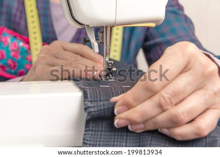 Closeup of seamstress hands working with clothing item on a sewing machine. Focus in the needle. - stock photo