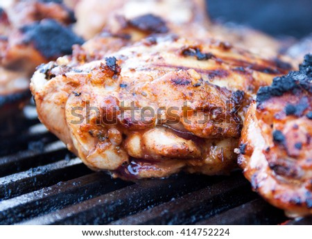 Closeup of seasoned and marinated chicken thighs being grilled on iron grates over charcoal - stock photo