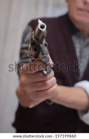 Closeup of senior couple fighting with a gun. - stock photo