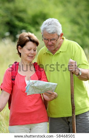 Closeup of senior couple rambling in countryside with map - stock photo