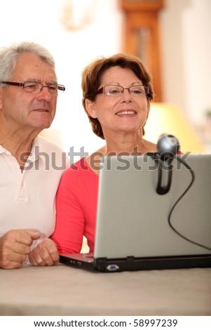 Closeup of senior couple sending messages through web cam - stock photo